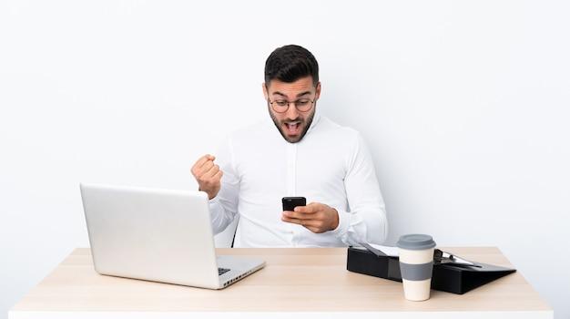 Молодой бизнесмен на рабочем месте удивлен и отправив сообщение