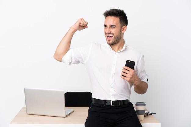 勝利を祝って職場で携帯電話を持つ青年実業家