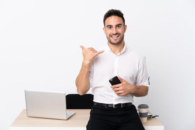 Молодой бизнесмен с мобильным телефоном на рабочем месте, делая жест телефона