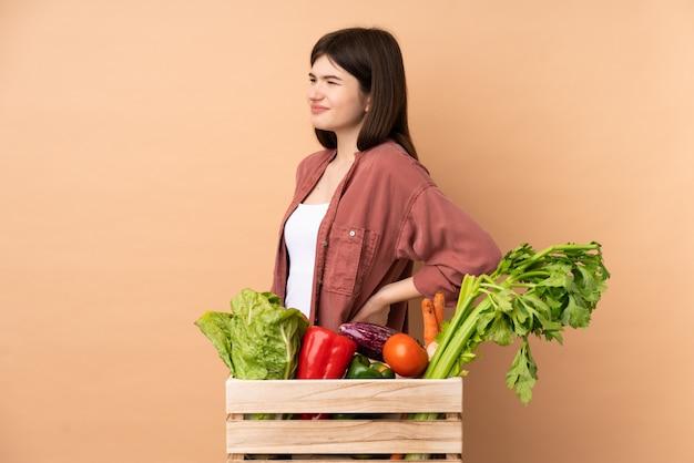 努力したため腰痛に苦しんでいるボックスで野菜を摘みたての若い農家の女性