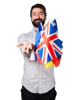 Красивый мужчина с бородой, держащей много флагов и представляя что-то
