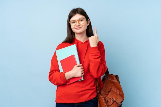Молодая женщина студента подростка держа салат указывая с указательным пальцем отличная идея