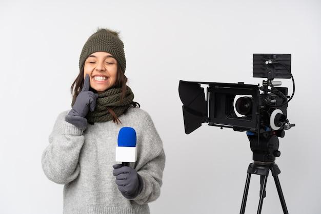 マイクを保持し、幸せで楽しい表情で笑顔のニュースを報告するレポーター女性