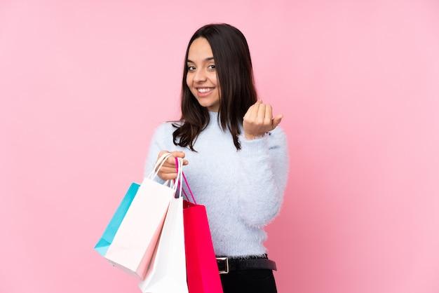手に来ることを誘って買い物袋を持つ若い女性。あなたが来て幸せ