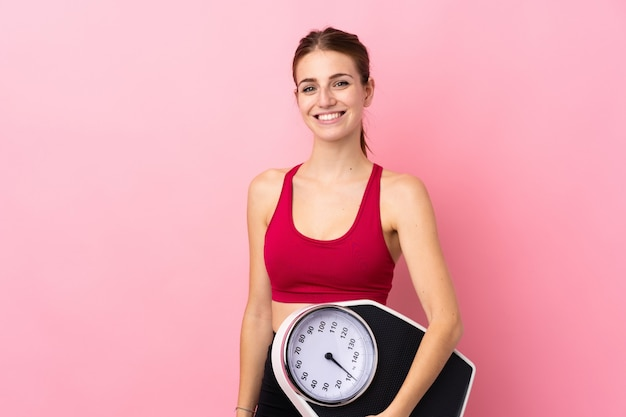 計量機で分離されたピンクの壁の上の若いスポーツ女性