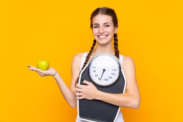 計量機とリンゴの分離の黄色の壁の上の若い女性