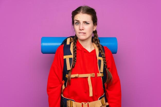 疑問を持っている分離された紫色の壁の上の大きなバックパックと混乱の表情を持つ若い登山家の女の子