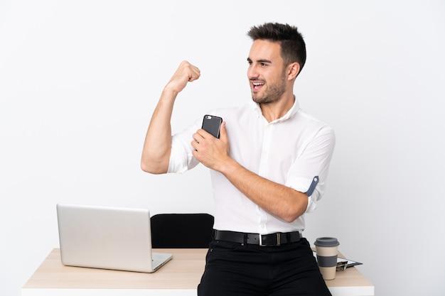 Молодой бизнесмен с мобильным телефоном на рабочем месте, делая сильный жест