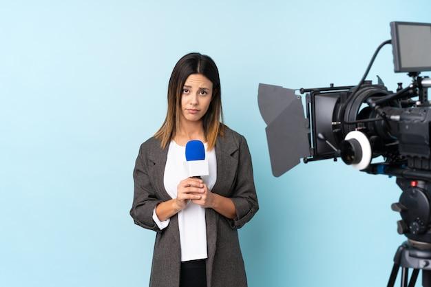 Репортер женщина держит микрофон и сообщая о новостях умоляя