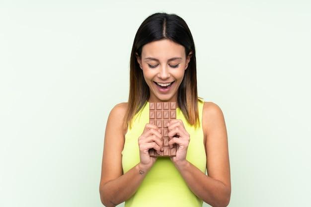 チョコレートタブレットを食べる女性