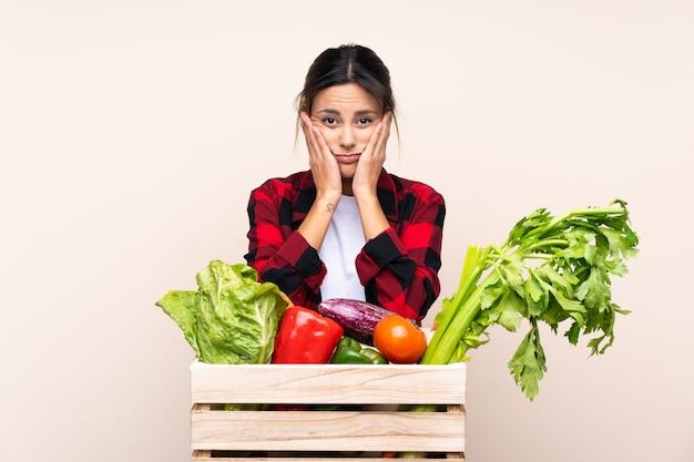 不幸で不満の木製バスケットで新鮮な野菜を保持している農家の女性