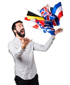 たくさんの旗を抱えているひげのある幸せなハンサムな男