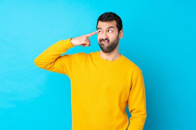 頭に指を置く狂気のジェスチャーを作る分離の青い壁の上の若い白人男