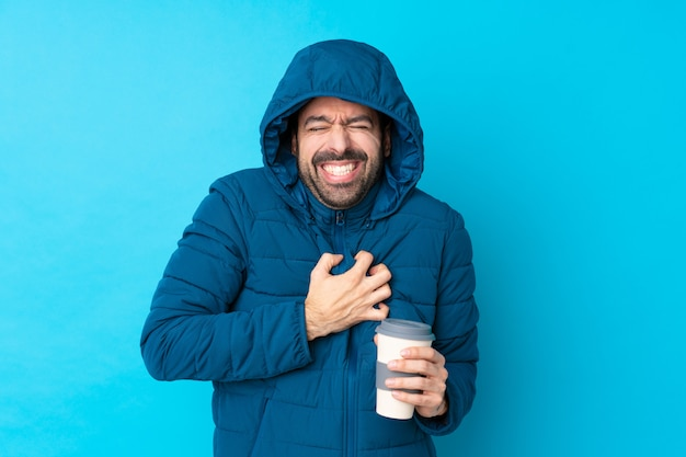 冬のジャケットを着て、心の痛みを持っている孤立した青い壁に持ち帰り用のコーヒーを保持している男