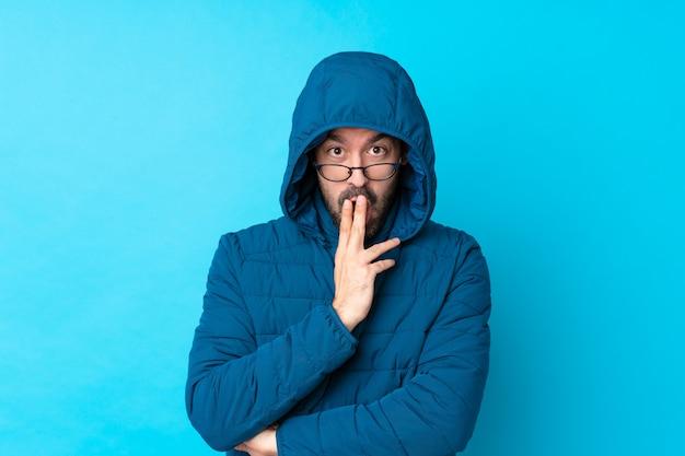冬のジャケットを着て、眼鏡と驚きの青い壁に持ち帰り用のコーヒーを保持している男
