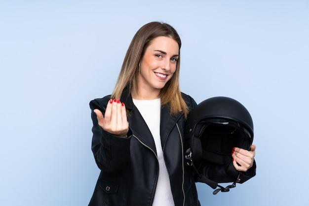 手で来ることを招待して孤立した壁の上のオートバイのヘルメットを持つ若いブロンドの女性。あなたが来て幸せ