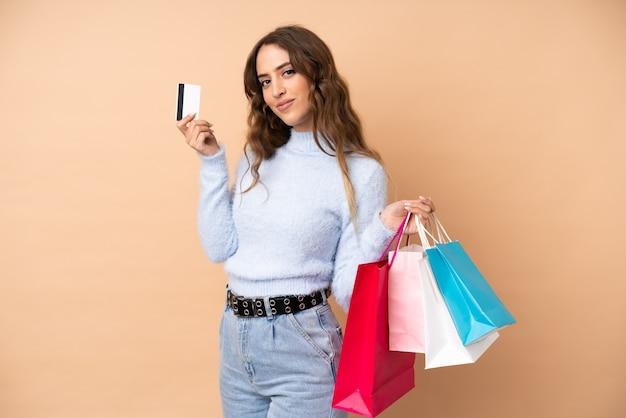 買い物袋とクレジットカードを保持している孤立した壁の上の若い女性