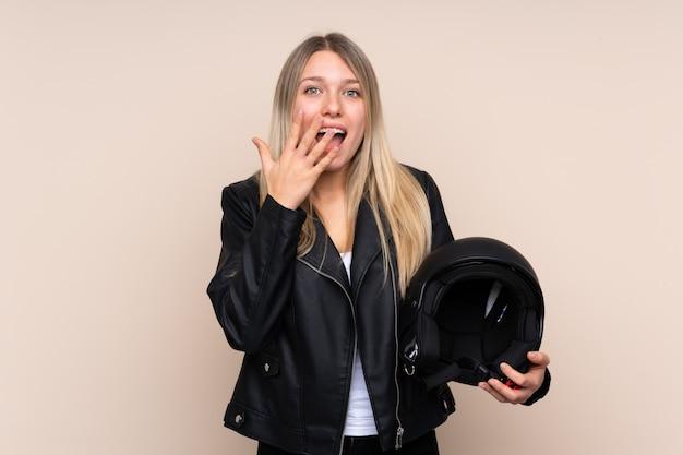驚きの表情で孤立した壁の上のオートバイのヘルメットを持つ若いブロンドの女性