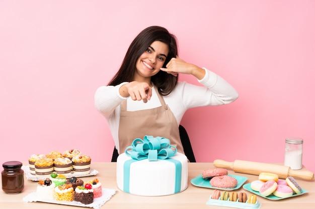 Шеф-кондитер с большой торт в таблице над изолированной розовой стеной, делая жест телефона и указывая вперед