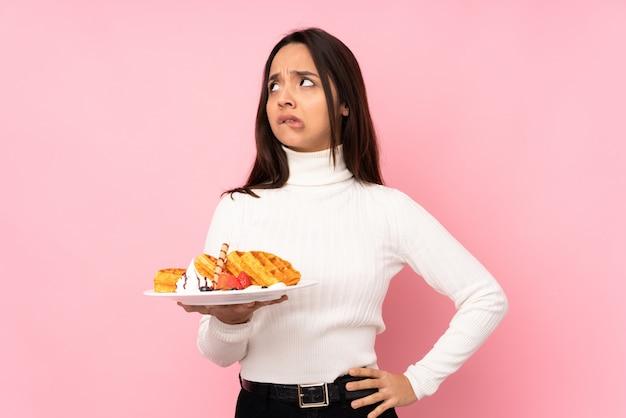 混乱の表情で孤立したピンクの壁にワッフルを置く若いブルネットの女性