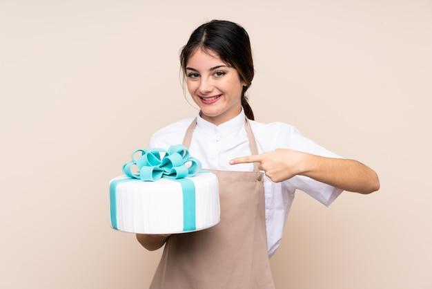 パティシエの女性が大きなケーキを押しながらそれを指す