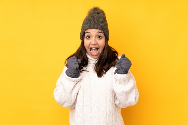 勝者の位置で勝利を祝う孤立した黄色の壁の上の冬の帽子を持つ若い女性