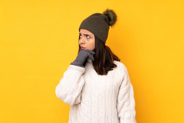 疑問を持つ混乱した表情と分離の黄色の壁の上の冬の帽子を持つ若い女性