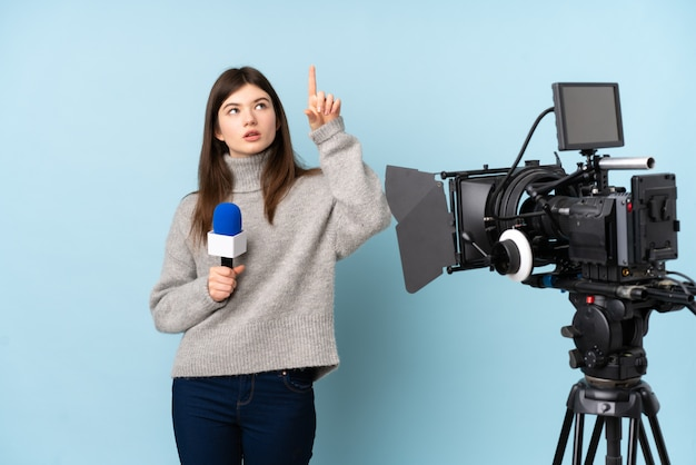 マイクを押しながら透明なスクリーンに触れるニュースを報告する若いレポーター女性