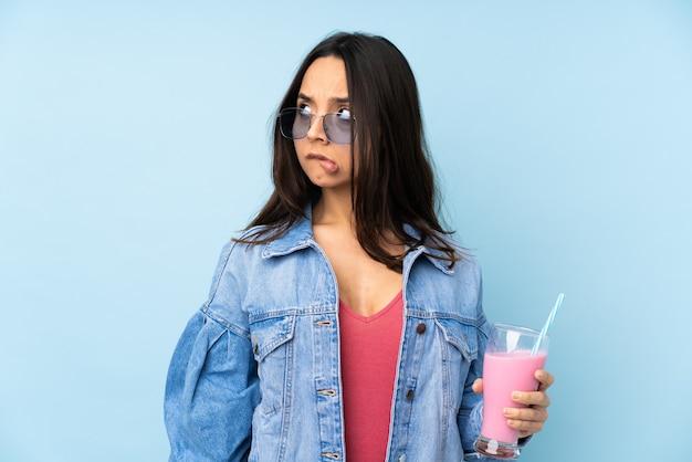 混乱の表情で孤立した青い壁にいちごのミルクセーキを持つ若い女性