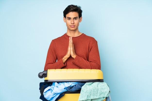 訴えかけるような服でいっぱいのスーツケースを持つ男
