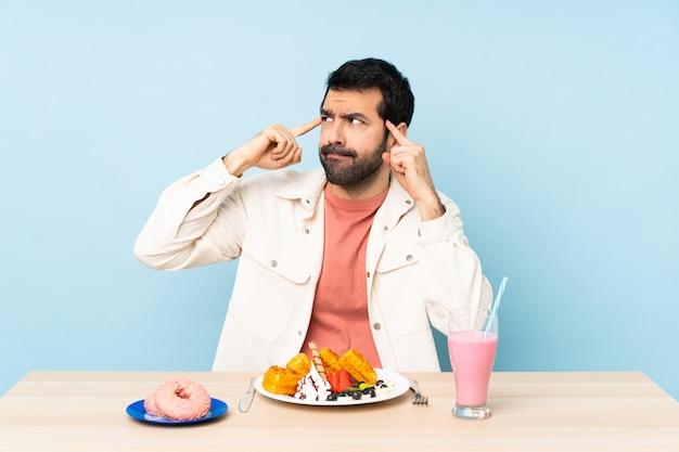 朝食ワッフルと疑問と思考を持っているミルクセーキを持つテーブルで男