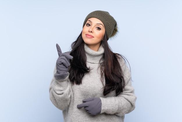 人差し指で素晴らしいアイデアを指している冬の帽子を持つ若いコロンビアの女の子