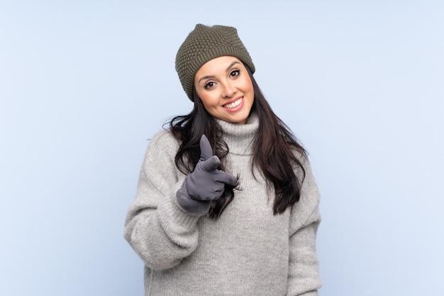 冬の帽子を持つコロンビアの少女はあなたに指を指す