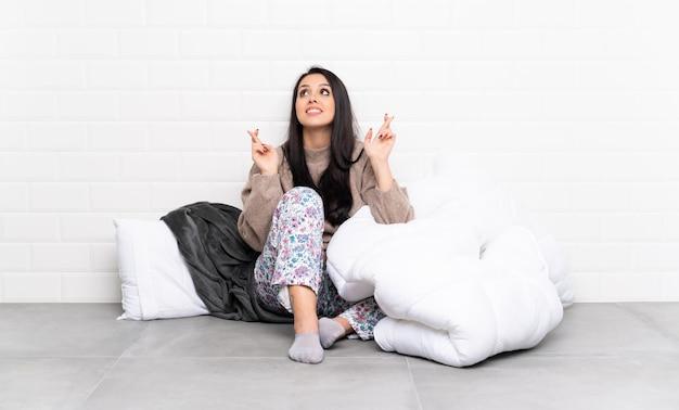 Молодая колумбийская девушка в пижаме в помещении, скрестив пальцы и желая лучшего