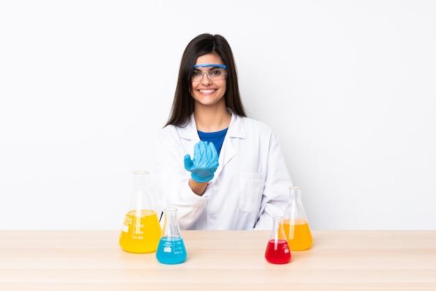 手に来るように誘うテーブルの若い科学的な女性。あなたが来て幸せ