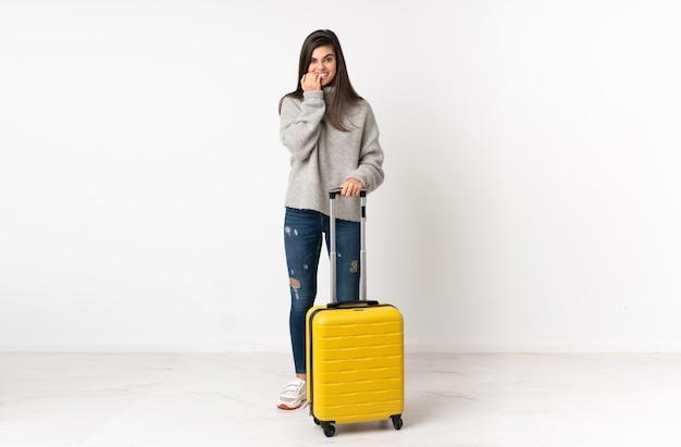 孤立した白い壁に神経質で怖いスーツケースを持つ旅行者女性の全身