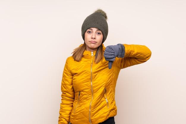 サインダウン親指を示す孤立した壁の上の冬の帽子を持つ女性