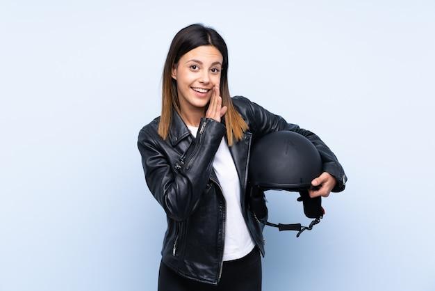 Молодая брюнетка женщина, держащая мотоциклетный шлем над синей стеной, что-то шепчет
