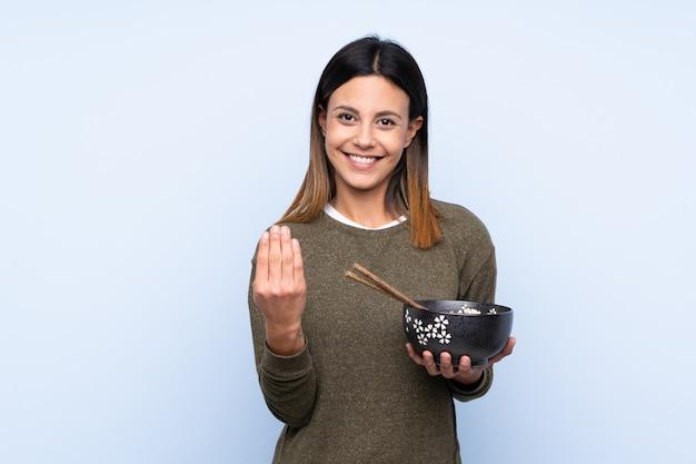 手で来ることを招待して孤立した青い壁の上の女性。お箸で麺を握りながら来てくれて幸せ
