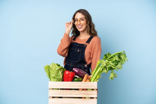 メガネと幸せなボックスで摘みたての野菜を持つ農家