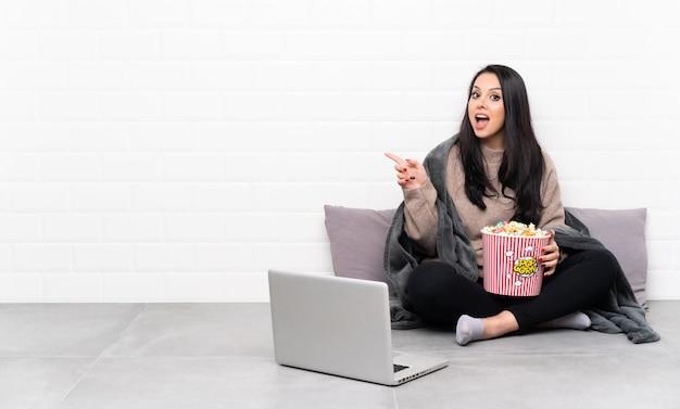 ポップコーンのボールを保持していると驚いたと側に指を指しているラップトップで映画を見せてコロンビア少女
