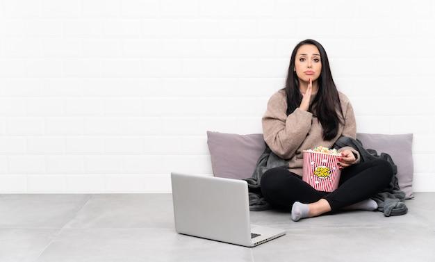 Молодая колумбийская девушка держит миску попкорна и показывает фильм в ноутбуке держит ладонь вместе. человек просит что-то