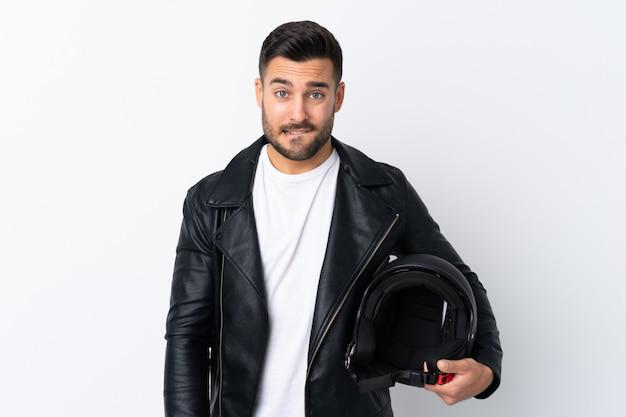 疑いのあるオートバイのヘルメットと混乱した表情を持つ男