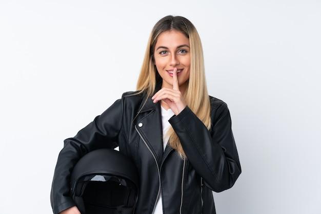 Молодая уругвайская женщина с мотоциклетным шлемом над изолированной белой стеной делает жест молчания