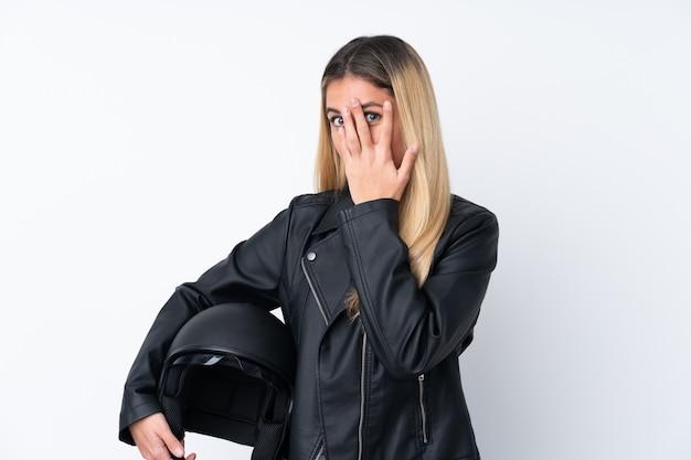 Молодая уругвайская женщина с мотоциклетным шлемом над изолированной белой стеной, покрывающей глаза и смотрящей сквозь пальцы