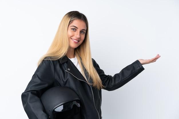 Молодая уругвайская женщина с мотоциклетным шлемом над изолированной белой стеной, протягивающей руки в сторону для приглашения прийти