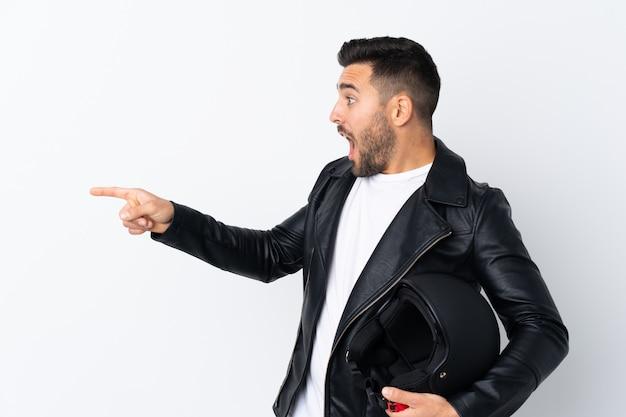 Человек с мотоциклетным шлемом, указывая пальцем в сторону