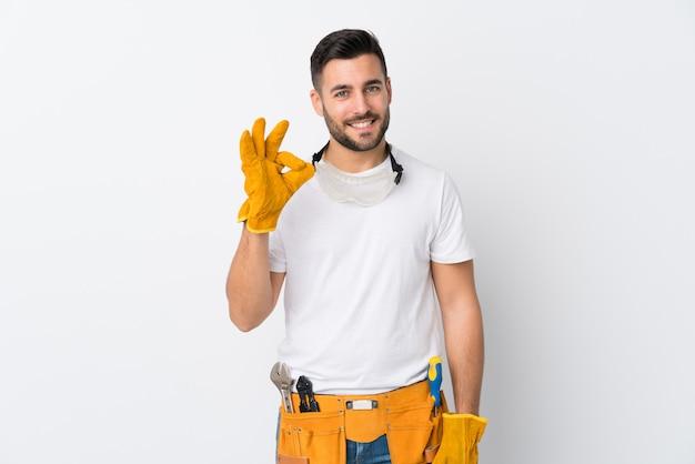 Ремесленники или электрик человек над изолированной белой стене, показывая знак ок с пальцами