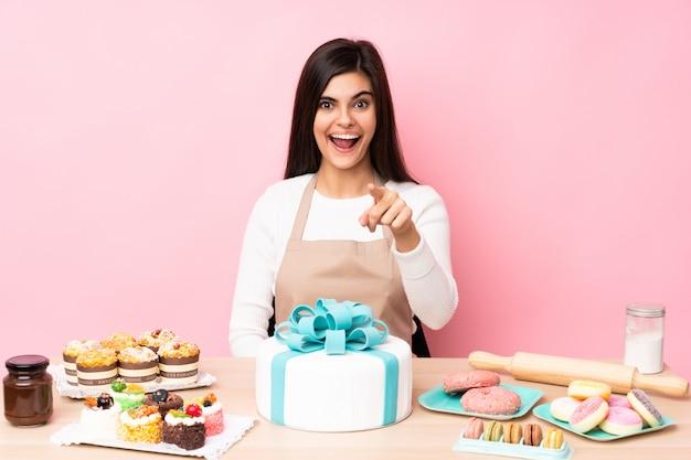 Шеф-кондитер с большим тортом в столе на розовой стене удивил и указал вперед