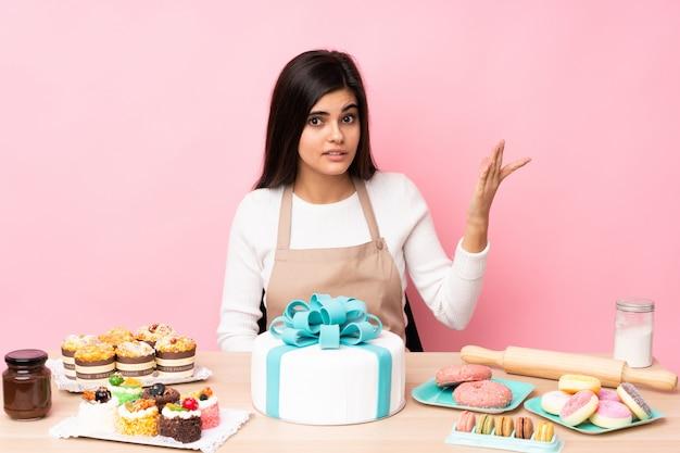 Шеф-кондитер с большим тортом в столе на розовой стене делает жест сомнения